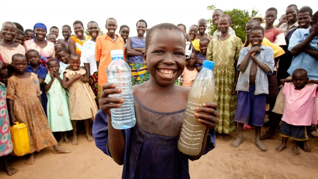 Boy holds water given by Charity: Water.
